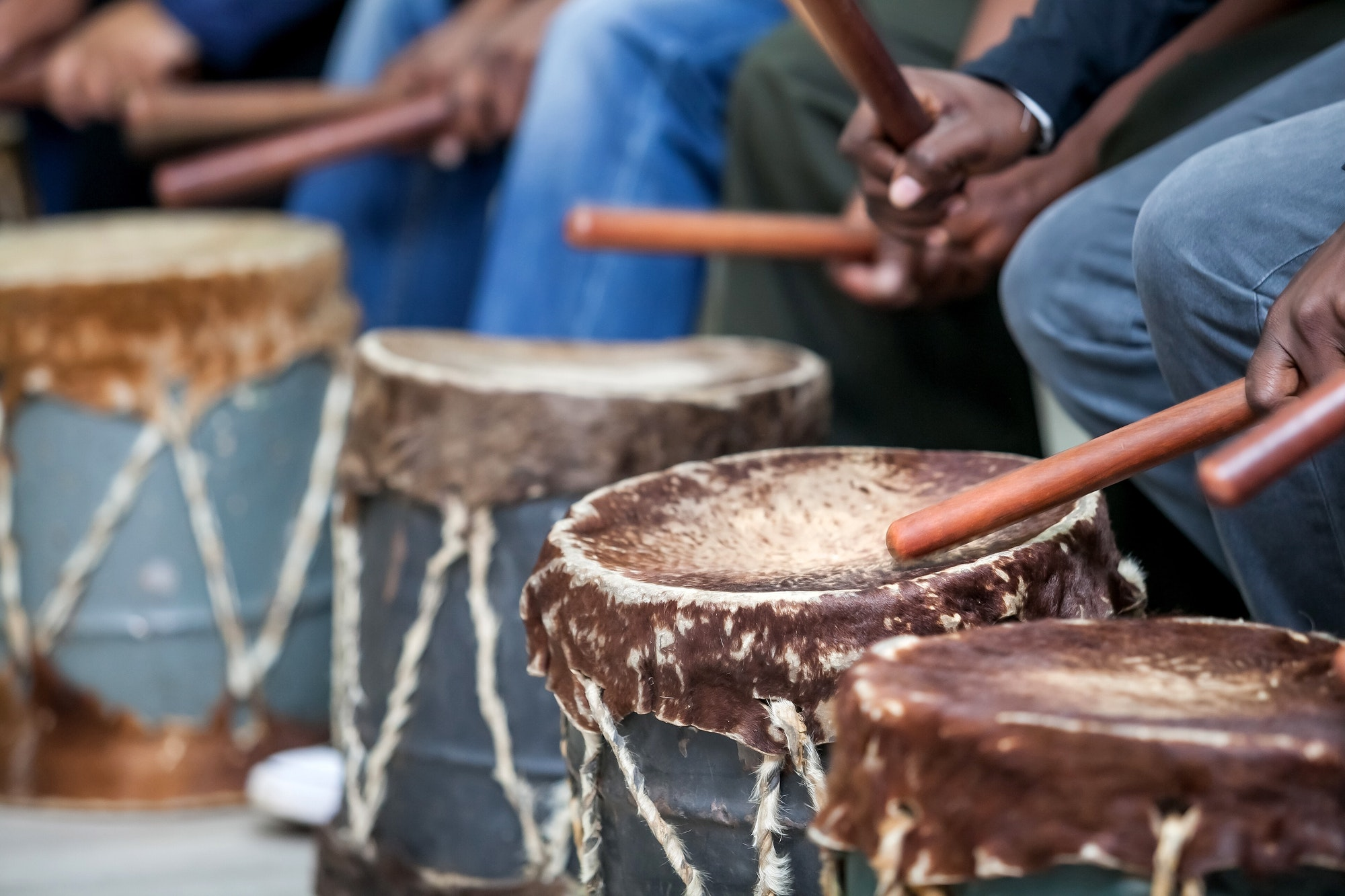 Drums being played with drum sticks. African Djembe drums